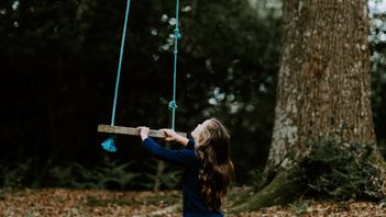 little girl playing in backyard with a homemade tree swing