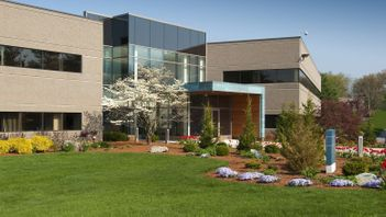 front of a commercial building with a beautiful landscape of trees shrubs and flowers