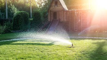 sprinkler system watering an Edmonton backyard trees and lawn at sunset