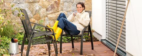 a woman sitting in her backyard enjoying a cozy cup of coffee